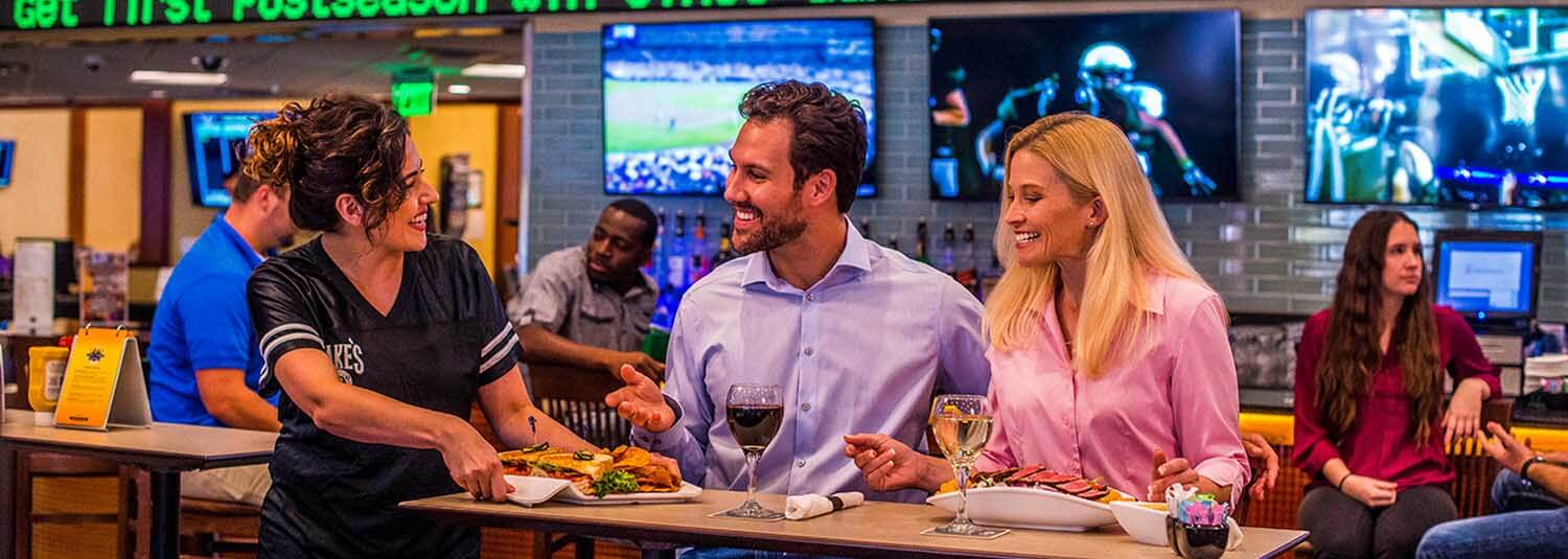 Server bringing food to couple, Jake's 29° Sports Bar & Grill